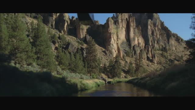 vídeos y material grabado en eventos de stock de air to air helicopter flying above canyon river - pared de roca