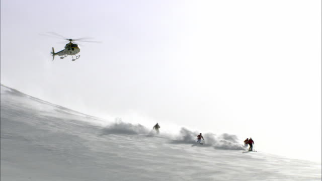 ws, helicopter flying above five skiers gliding down mountainside, cariboo and monashee mountains, british columbia, canada - helicopter tour stock videos and b-roll footage