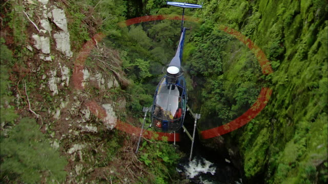 air to air, helicopter flying above forest and mountain river, fiordland national park, new zealand - helikopter bildbanksvideor och videomaterial från bakom kulisserna