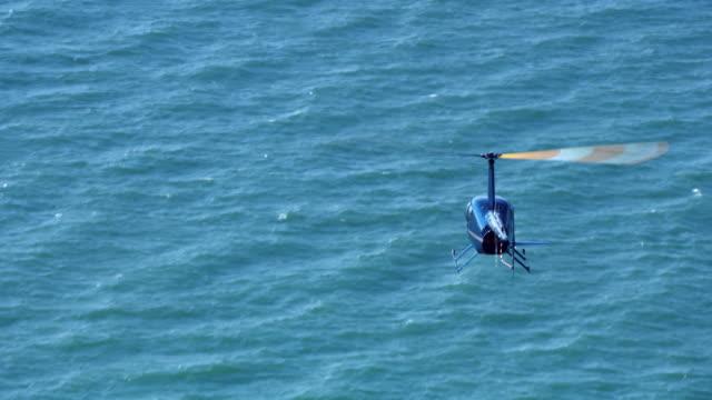 stockvideo's en b-roll-footage met luchtfoto helikopter vliegen boven de zee in de zon - sunny