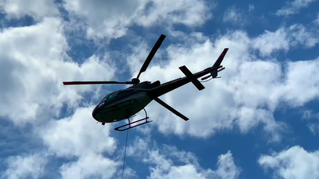 helicopter flying against blue sky and clouds - helicopter stock videos & royalty-free footage