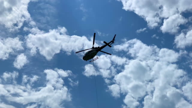 helicopter flying against blue sky and clouds - audio available点の映像素材/bロール