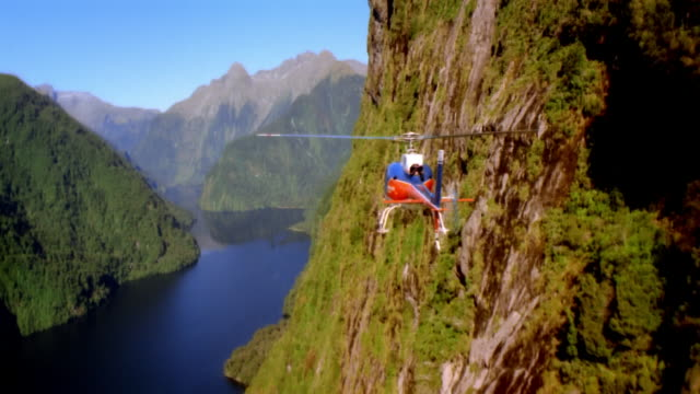 stockvideo's en b-roll-footage met air to air, helicopter flying along canyon river, rear view, new zealand - exploration