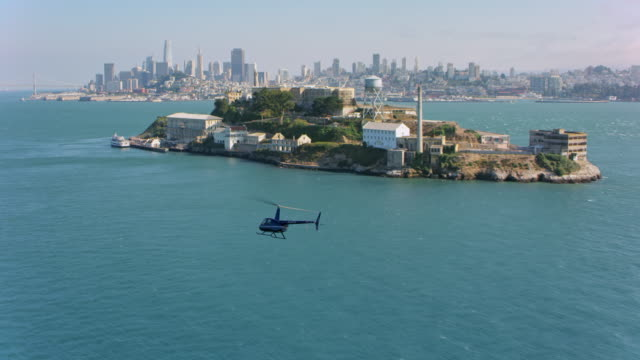 vídeos de stock e filmes b-roll de aerial helicopter flying along the alcatraz island with san francisco in the background - helicóptero