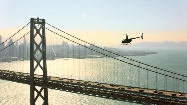 バック グラウンドでサンフランシスコ ダウンタウンを見下ろす San サンフランシスコ ・ オークランド ・ ベイブリッジに沿って飛んで空中のヘリコプター