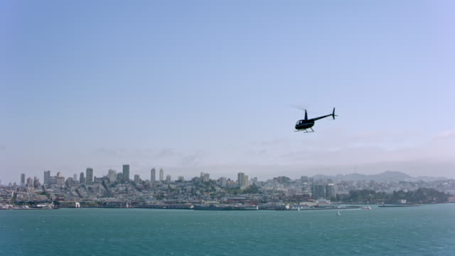 vídeos de stock e filmes b-roll de aerial helicopter flying in the san francisco bay overlooking the city on a sunny day. - helicóptero