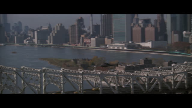 air to air, helicopter flying over queensboro bridge, city skyline in background, new york city, new york, usa - レターボックス点の映像素材/bロール