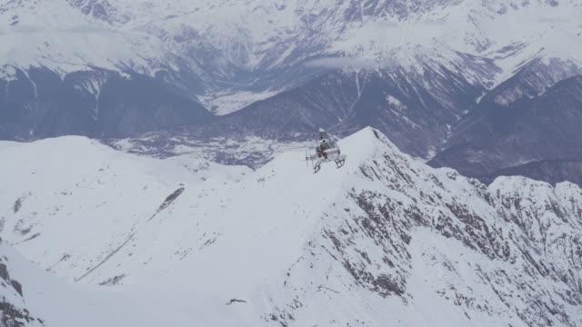hubschrauber fliegen über schneebedeckte berge - georgia stock-videos und b-roll-filmmaterial