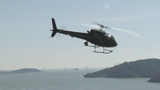 aerial helicopter flying over still waters of the san francisco bay, rocky shoreline beyond / san quentin, california, united states - hovering stock videos & royalty-free footage