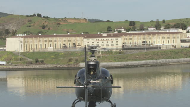 vídeos de stock, filmes e b-roll de aerial helicopter flying over still waters of the san francisco bay, the state prison, and the courtyard beyond / san quentin, california, united states - baía de são francisco