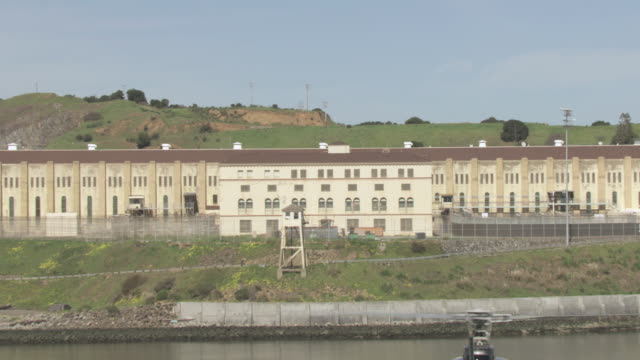 vidéos et rushes de aerial helicopter flying over still waters of the san francisco bay, the state prison, and the courtyard beyond / san quentin, california, united states - bay of water