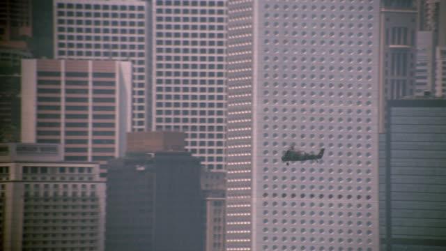 stockvideo's en b-roll-footage met helicopter flying past buildings in hong kong / central district - stadscentrum hongkong hongkong