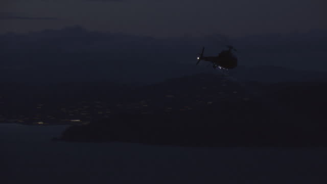 ts a helicopter flying through night sky and casting searchlight over harbor and city skyline / san francisco, california, united states - searchlight stock videos & royalty-free footage