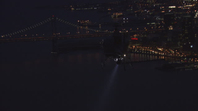 ts a helicopter flying through night sky and casting searchlight over san francisco bay / california, united states - helicopter tour stock videos and b-roll footage