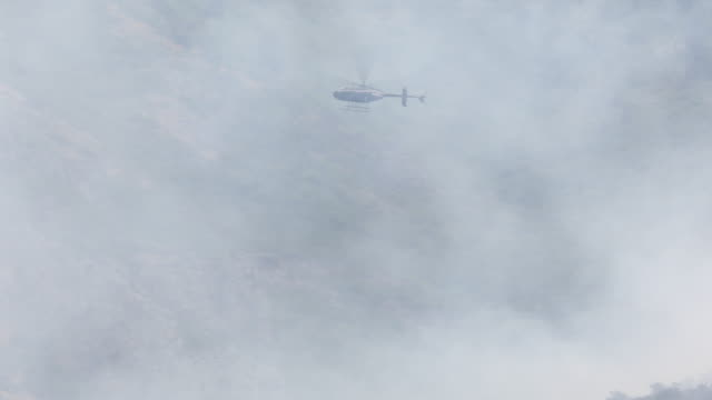 vídeos y material grabado en eventos de stock de helicopter flying through smoke of wildfire - provo