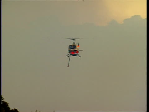 ms helicopter flying to camera, dumping water on bushfire - australien stock-videos und b-roll-filmmaterial