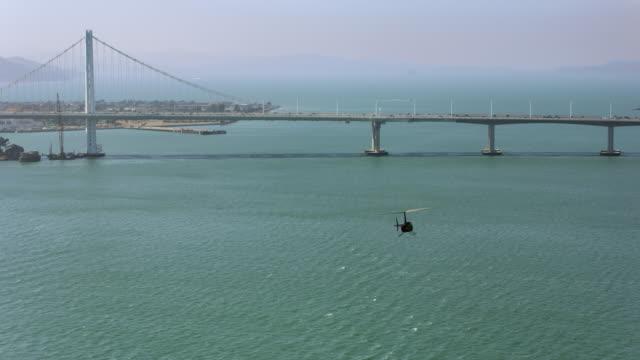 San サンフランシスコ ・ オークランド ・ ベイブリッジのドワイト ・ D ・ アイゼンハワー高速道路に向かって飛んで空中のヘリコプター