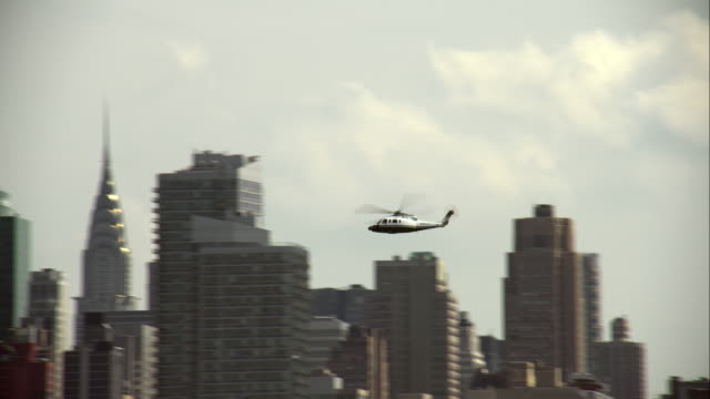 helicopter flying up hudson river with manhattan in the background - ヘリコプター点の映像素材/bロール