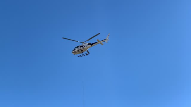 helicopter flying with steel cable against clear blue sky in a sunny day - hovering stock videos & royalty-free footage