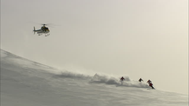A helicopter follows five skiers as they speed down a mountain.