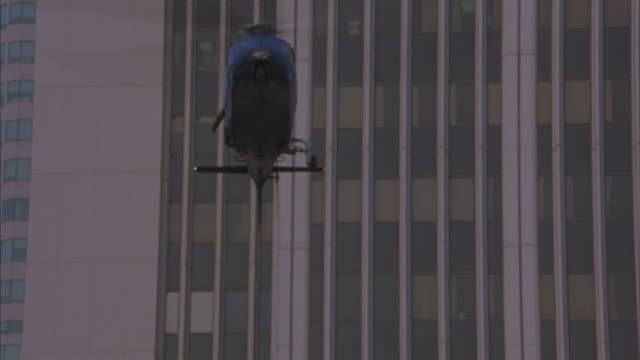 a lapd helicopter hovering between city buildings, emitting smoke, and spinning out of control. - los angeles police department stock videos & royalty-free footage