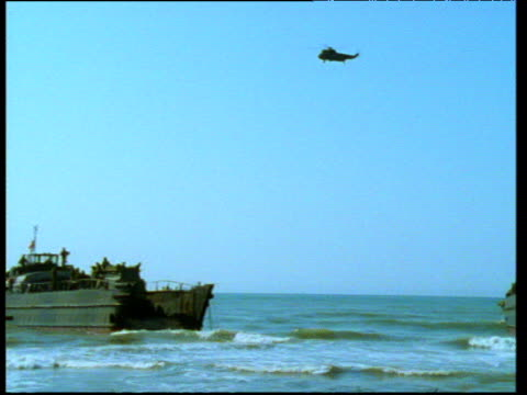 vídeos de stock, filmes e b-roll de helicopter hovers above amphibious craft launched by us army. - veículo anfíbio