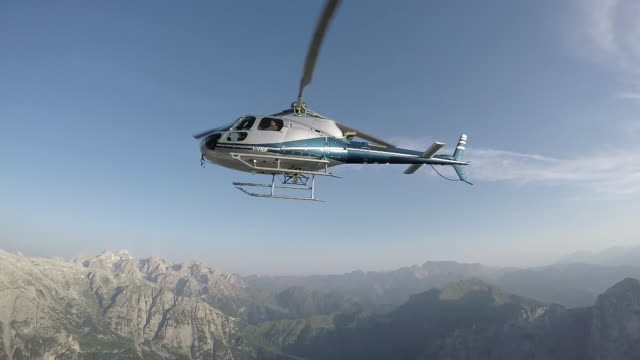 vídeos de stock e filmes b-roll de helicopter hovers above cliff, men hanging onto cable - cable