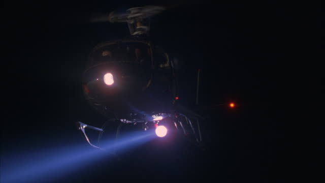 a helicopter hovers in a black sky shining a search light downward. - helicopter stock videos and b-roll footage