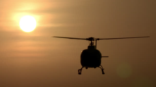 A helicopter hovers in front of the sun, then flies away.