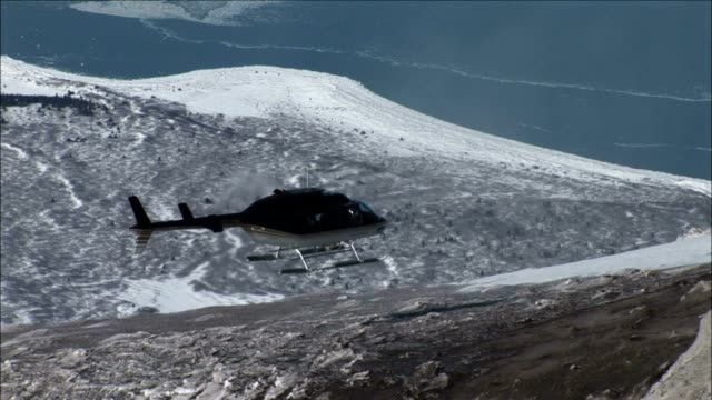 vídeos de stock e filmes b-roll de a helicopter hovers over a snowy mountain. - helicóptero