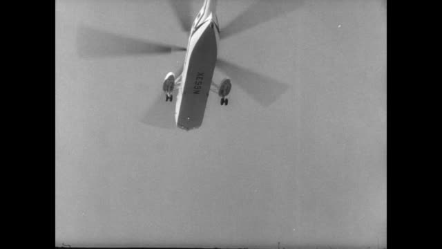 helicopter in front of heliport building at 1964 new york world fair / helicopter coming into land / crowd on helipad look at the skyline /... - ネルソン a ロッカフェラー点の映像素材/bロール
