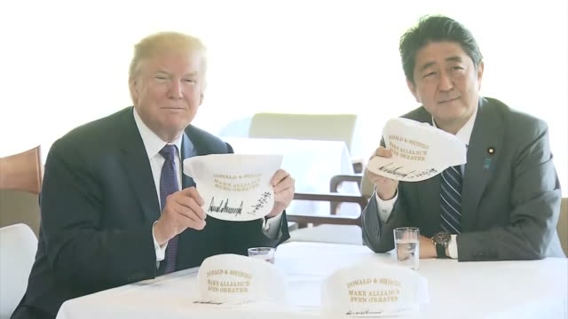 Helicopter landing at Saitama Trump getting out of the helicopter Trump walking over to Abe Abe and Trump shaking hands Abe and Trump walking away...