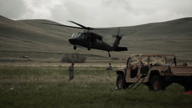helicopter landing in field with surrounding humvee and soldiers - army stock-videos und b-roll-filmmaterial
