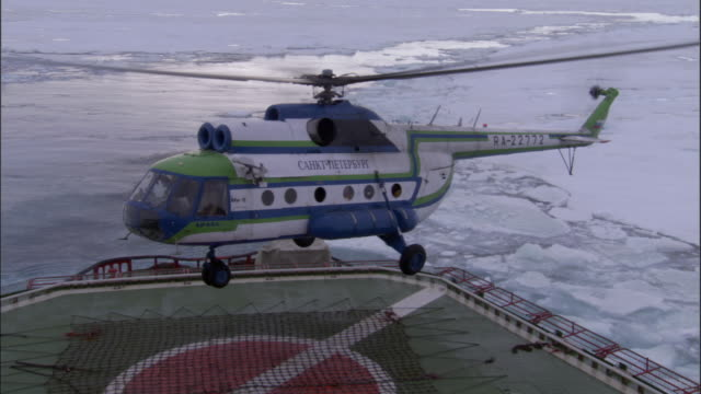 ms, helicopter landing on helipad of icebreaker traveling through broken pack ice, russia - helicopter landing stock videos & royalty-free footage