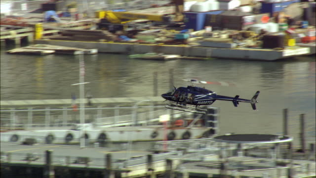 air to air helicopter landing on helipad on east river, manhattan skyline in background / new york city, new york, usa - air to air shot stock videos & royalty-free footage