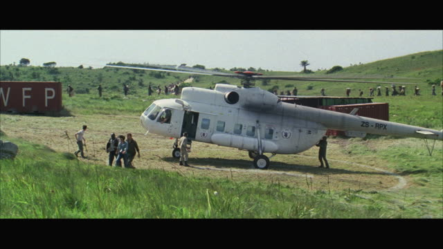 WS Helicopter (MI-8) landing on open field, refugees in background