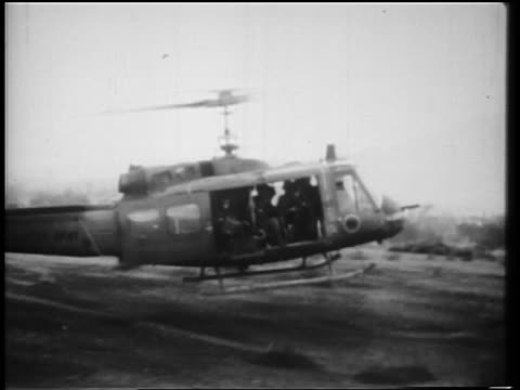 b/w 1966 helicopter landing soldiers starting to get out in countryside during vietnam war - 1966年点の映像素材/bロール