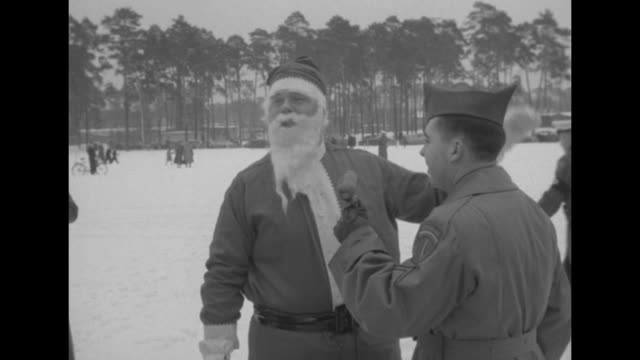 Helicopter lands on snowy ground / Santa Claus carrying a large cloth bag gets out of helicopter walks and waves / VS Santa talks to military...