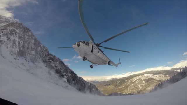 a helicopter lands to pick up skiers in the mountains. - time-lapse - helicopter tour stock videos and b-roll footage
