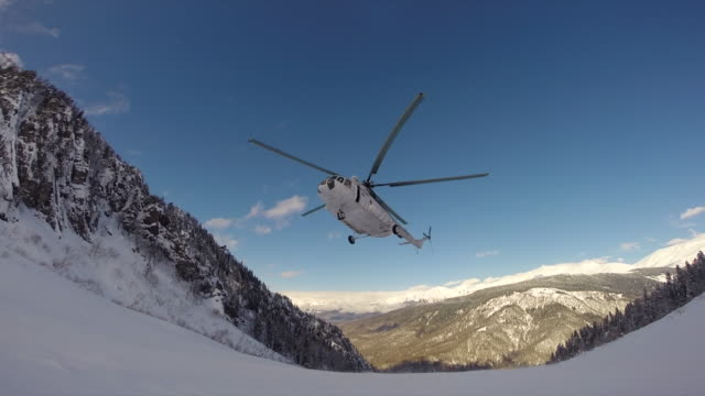 vídeos de stock e filmes b-roll de a helicopter lands to pick up skiers in the mountains. - helicóptero