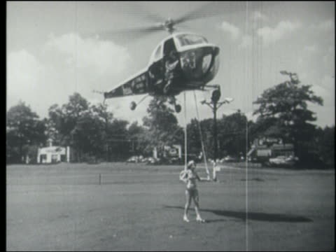 b/w helicopter lifting woman off ground / nyc - stunt person stock videos & royalty-free footage
