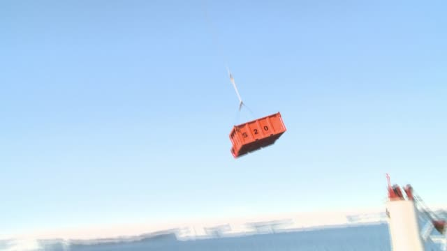 A helicopter lifts a giant container from a cargo ship and ascends into a blue sky. Available in HD.