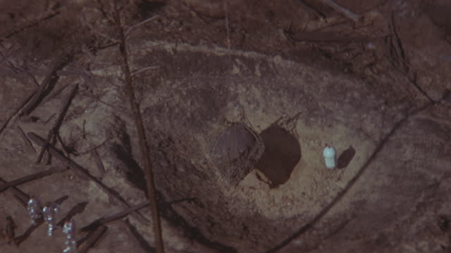 a helicopter lifts an object out of a crater. - ufo stock-videos und b-roll-filmmaterial