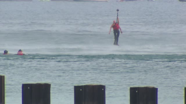 helicopter lifts drowning victim during practice water rescue at the chicago air and water show on august 17, 2014 in chicago, illinois. - chicago air and water show stock videos & royalty-free footage