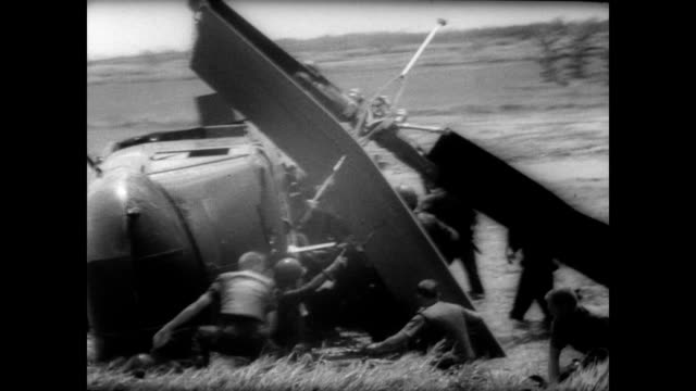 us helicopter on its side in a rice paddy with american soldiers running for cover / arial shots of smoke billowing from the landscape / ground view... - vietnam bildbanksvideor och videomaterial från bakom kulisserna