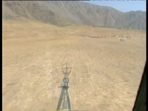 helicopter on landing approach to remote airfield amidst gunships during tajikistan civil war 1992 - kampfhubschrauber stock-videos und b-roll-filmmaterial
