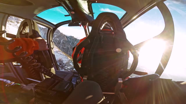 POV helicopter passenger behind the pilot flying into the sun