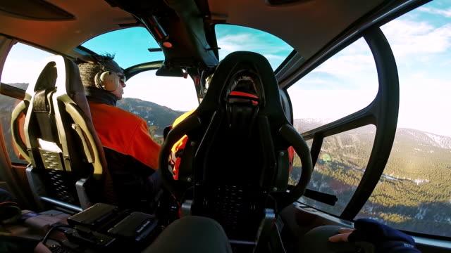 pov hubschrauber passagier blick in pilot fliegt über einem forest - flugzeugperspektive stock-videos und b-roll-filmmaterial