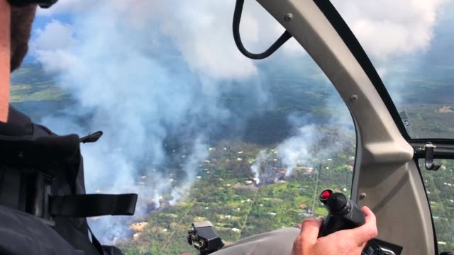 a helicopter passes above volcanic gases mixed with smoke rising from fires caused by lava in the leilani estates neighborhood in the aftermath of... - kilauea stock videos & royalty-free footage