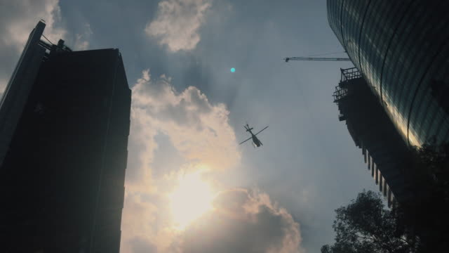 Helicopter passing by modern buildings in downtown Mexico City